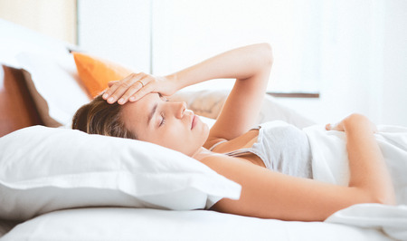Woman with headache in bed Stock Photo