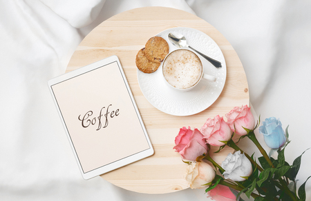 Breakfast in bed with cappuccino, cookies, tablet and flowers