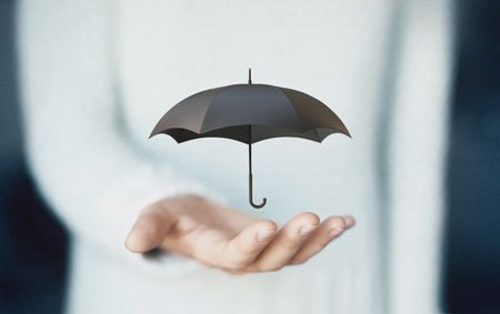 Umbrella on hands, concept of insurance or rain