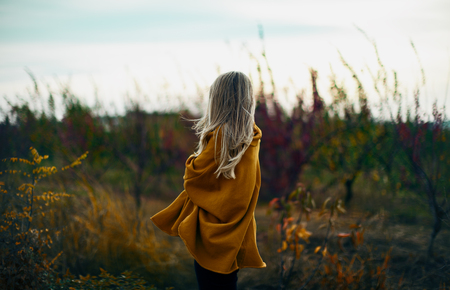 Woman in an autumn field with wind and leaves Standard-Bild - 111369411