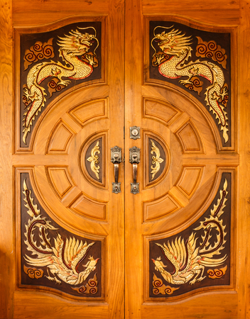 door handles: Wood door with dragons and swans design Stock Photo