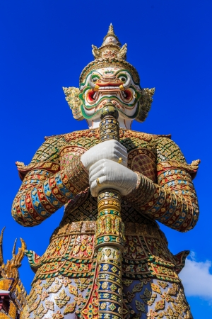 The statue of giant hold club and blue sky in Wat Phra Kaew ,Thailand   Ant