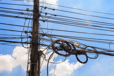 electricity post with untidy wire and blue sky Stock Photo - 23574117
