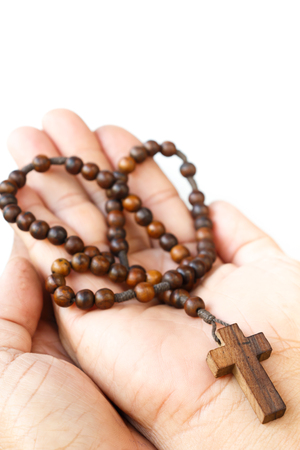 revere: wood rosary with cross on palm of human