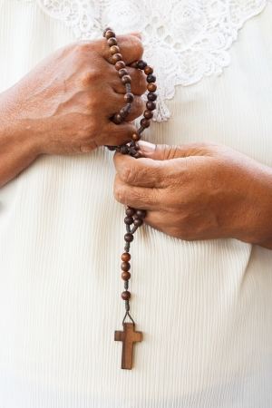 revere: asian in white cloth hold a rosary for pray to god