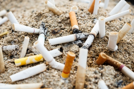 cinders: many burnt cigarettes on ashtray and sand