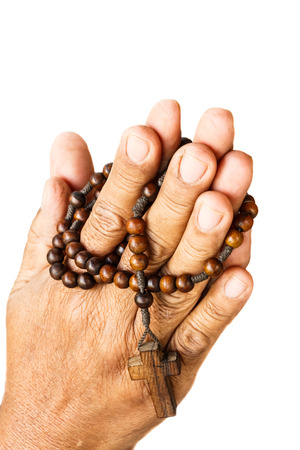 rosary beads: hands of old aged human were binded by wood rosary on white background (isolated) Stock Photo