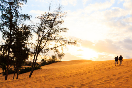 twin asian human are walking on Mui Ne sand dune when sunset ,South Vietnam photo