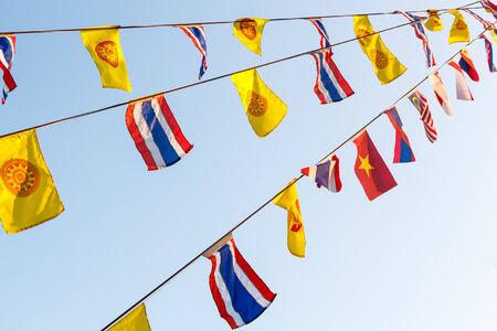 dhamma: Bandiere nazionali e Wheel of bandiere Dhamma 's su stringa e cielo blu a Chiangrai, Thailandia Archivio Fotografico