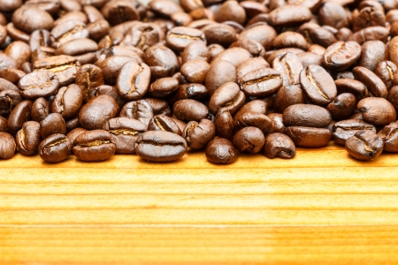 crop margin: Close up of coffee beans on upper side and blank area at lower side on wooden table