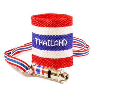 disharmony: Whistle and wristband in thai flag pattern (symbol of resistance to thai government) on white background (isolated) and blank area at right side Stock Photo