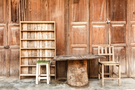 Wooden table,chairs,shelf in front of wooden house  rural scene  at Chiang Khan ,Thailand photo