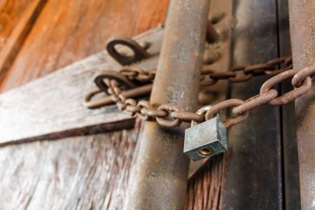 rusty chain and master key lock wood door photo
