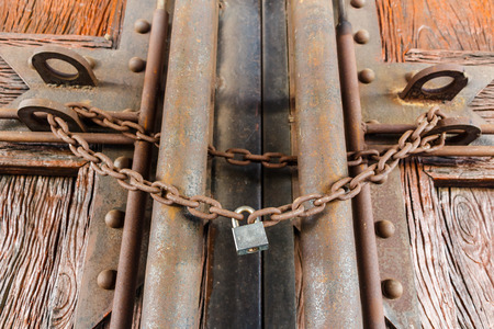 rusty chain and master key lock wood door photo