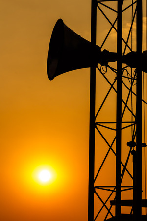 loudspeaker on pillar and sunset in the evening  silhouette  in Thailand photo