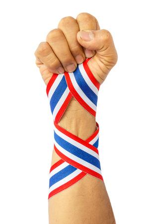 disharmony: thai man fist and bind thai flag pattern ribbon on forearm on white Stock Photo