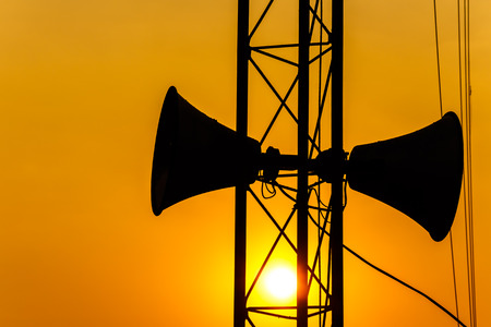 loudspeaker on pillar and sunset in the evening (silhouette) in Thailand photo