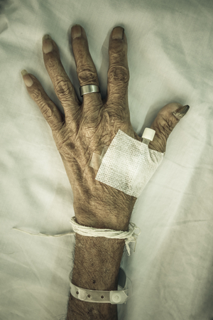 atrophy: hand of old patient with plug on bed in hospital  vignette style