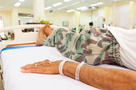 elderly patient lie down on bed in emergency room in rural hospital ,Thailand