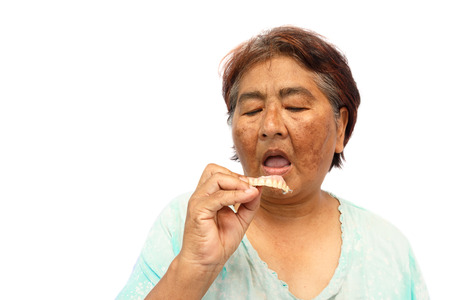 Old hoary woman open mouth and prepare to put a denture ( isolated background ) Stock Photo