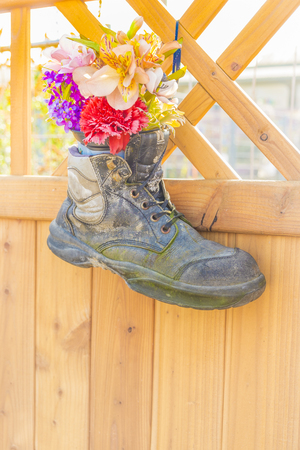 artifical: old used safety shoe bearing a bouquet of flowers artifical