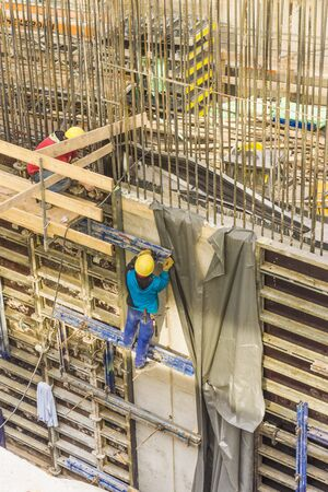 reinforcing bar: construction worker  without proper safety equipment