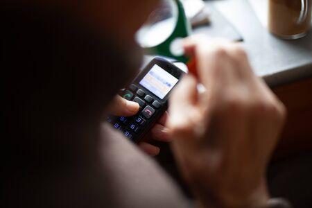 Old man uses mobile phone closeup