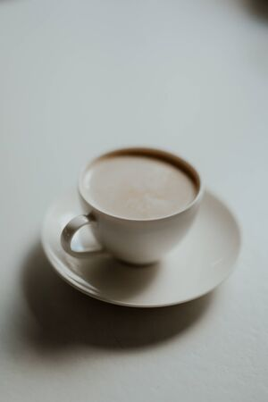 Cup of coffee in small white cup. Symbolic image. Bright background. Close up. Copy space.