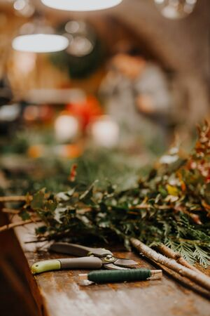 Top down view of florist's worktable. Handmade xmas decorations. Making rustic christmas wreath. Authentic rural wreath