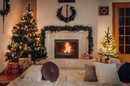 Gemütliches Wohnzimmer, Lichter, die bereit sind, Weihnachten zu feiern. Weihnachtsrauminnenraum, Weihnachtsbaum verziert mit Lichtern, Kerzen und Beleuchtungsgirlanden im Innenkamin.