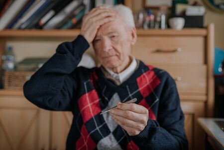 Senior Elderly Man Holding thermometer in Hands.