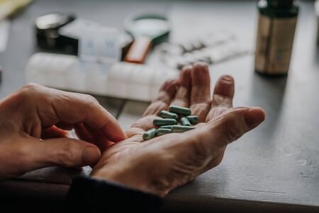 Old man holding handful of green pills in hand