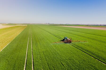 Farmer Spraying Pesticides on Agricultural Field. Tractor Spraying Young Corn with Fertilizer.