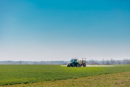 Spraying machine working on the green field Spraying Field with Herbicides and Pesticides GMO Fertylizer. Tractor Working in Field.