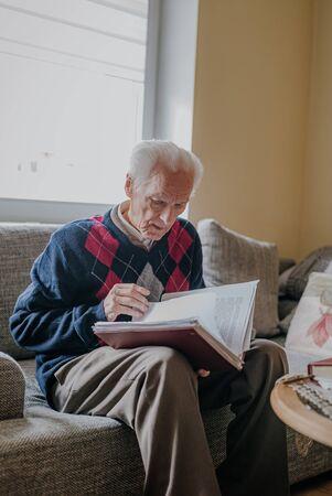 Elderly man reading book at home Фото со стока