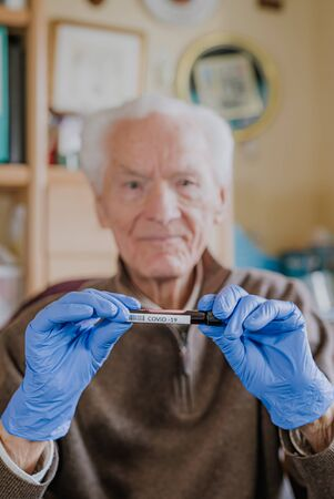 Old man holding Covid-19 sample