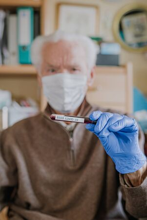 Old man wearing mask, holding Covid-19 sample