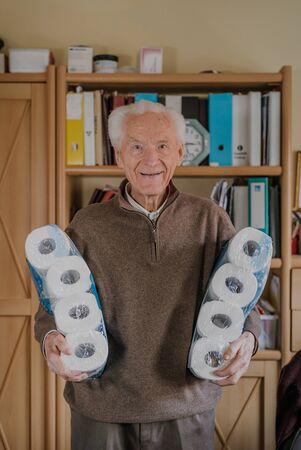 Old man holding two packs of toilet paper Фото со стока