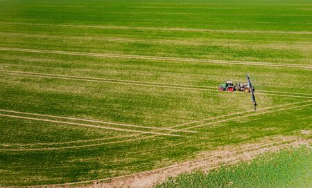 tractor spraying herbicides on field, Tractor Spraying Chemicals on Field - GMO Crops.