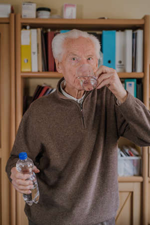 Portrait elderly man drinking water