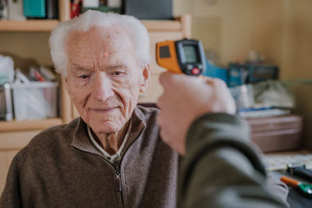 Old man measured temperature with thermometer