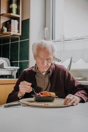 Single senior eats dinner at home