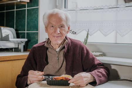 Portrait senior eats dinner at home