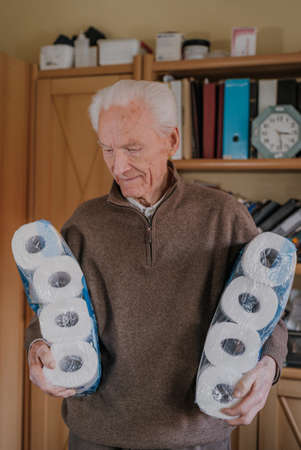 Old man holding two packs of toilet paper Stockfoto