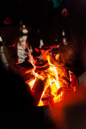 roasting sausages over fire in winter