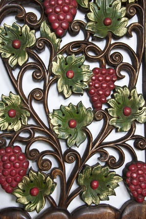 Pattern of grape carve with wooden on white wall background. photo