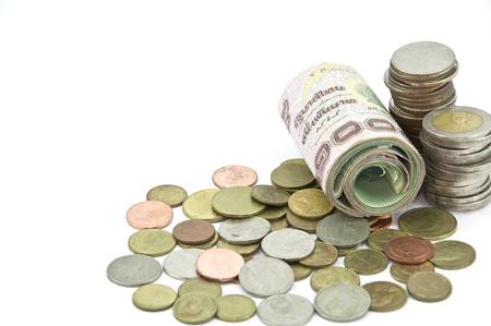 rouleau de mille baht tha�landais billets et de pi�ces de monnaie sur fond blanc
