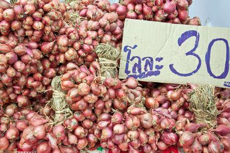 Tas de prix oignons rouges 30 bahts par kilogramme sec Banque d'images