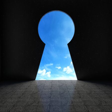 empty keyhole: Keyhole looking out into blue sky Stock Photo