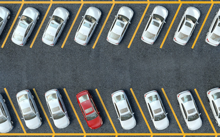 白い車の間で停車中の赤い車。車は駐車場に